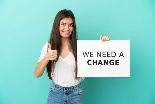 テキストとプラカードを保持している青い背景で隔離の若い白人女性私たちは親指を上にして変更が必要です