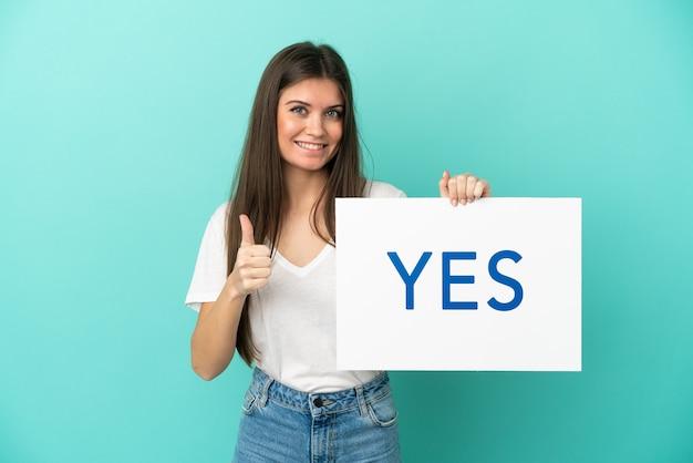 엄지 손가락으로 예 텍스트와 현수막을 들고 파란색 배경에 고립 된 젊은 백인 여자