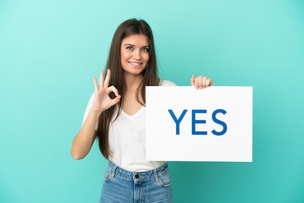 テキストyesのプラカードを保持している青い背景で隔離の若い白人女性