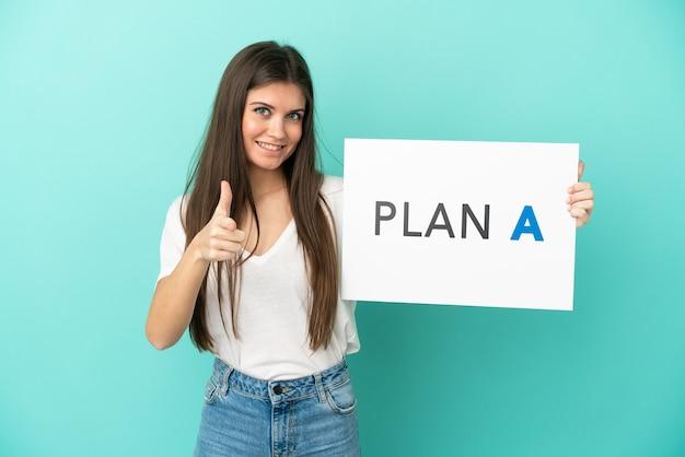 메시지 계획 a와 현수막을 들고 앞을 가리키는 파란색 배경에 고립 된 젊은 백인 여자