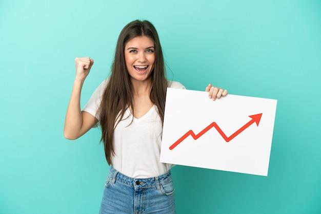 성장 통계 화살표 기호로 기호를 들고 승리를 축하 파란색 배경에 고립 된 젊은 백인 여자