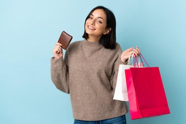 Молодая кавказская женщина изолирована на синем фоне, держа хозяйственные сумки и кредитную карту