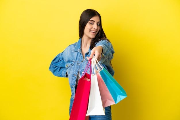 Молодая кавказская женщина изолирована на синем фоне, держа хозяйственные сумки и давая их кому-то