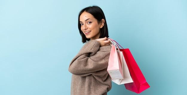ショッピングバッグを保持し、笑顔の青い背景で隔離の若い白人女性