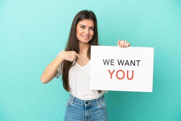 Молодая кавказская женщина изолирована на синем фоне, держа доску we want you и указывая на нее