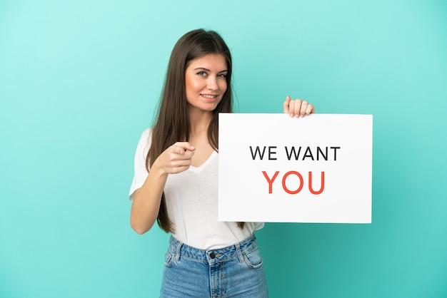 Молодая кавказская женщина, изолированная на синем фоне, держит доску we want you и указывает вперед