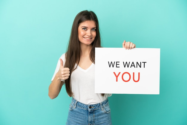 Молодая кавказская женщина изолирована на синем фоне, держа доску мы хотим, чтобы ты поднял палец вверх
