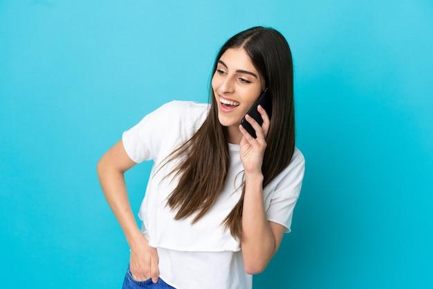 누군가와 휴대 전화로 대화를 유지하는 파란색 배경에 고립 된 젊은 백인 여자