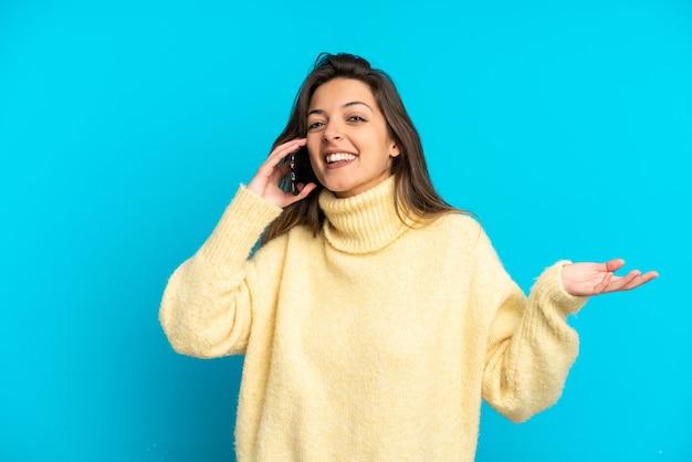 파란색 배경에 격리된 백인 젊은 여성이 누군가와 휴대전화로 대화를 나누고 있다