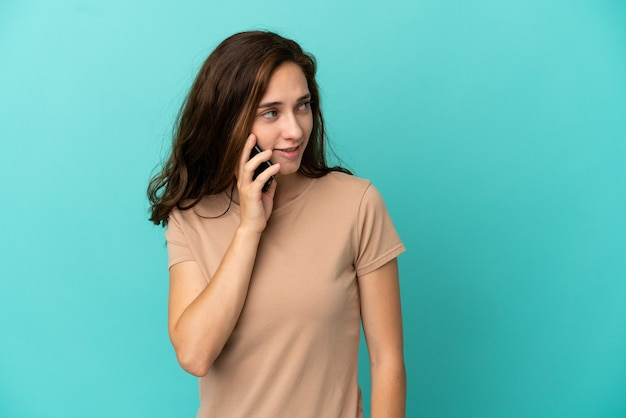 誰かと携帯電話で会話を続けている青い背景で隔離の若い白人女性