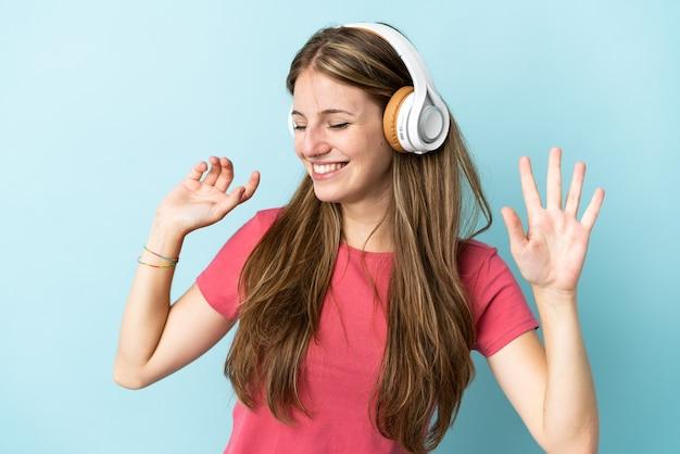 Молодая кавказская женщина изолирована на синем фоне, слушает музыку и танцует
