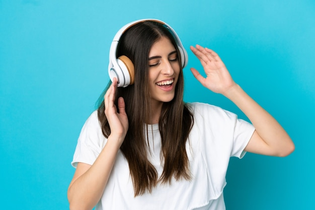 Молодая кавказская женщина изолирована на синем фоне, слушает музыку и поет
