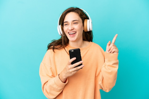 Молодая кавказская женщина изолирована на синем фоне, слушает музыку с мобильного телефона и поет