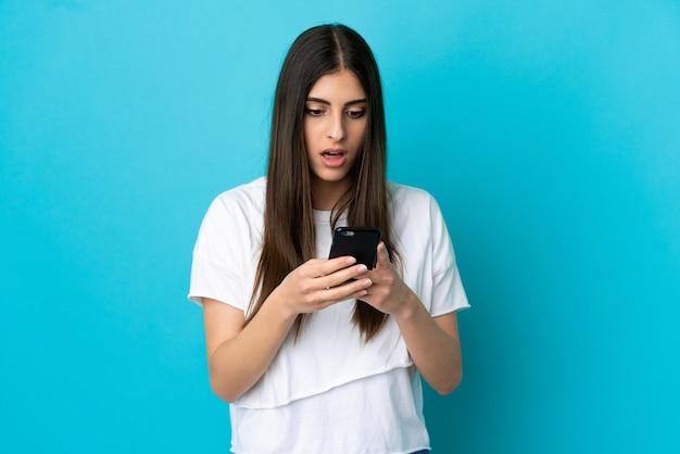 놀란 표정으로 모바일을 사용하는 동안 카메라를 찾고 파란색 배경에 고립 된 젊은 백인 여자