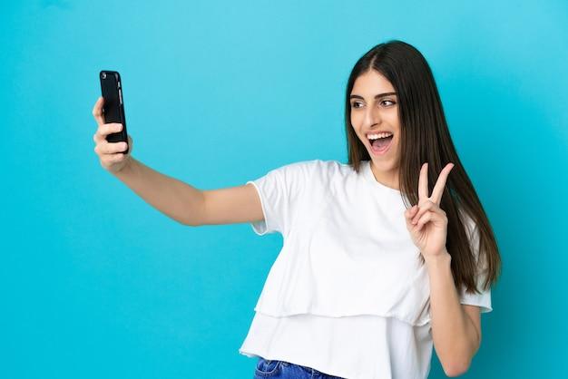 携帯電話でselfieを作る青い背景で隔離の若い白人女性
