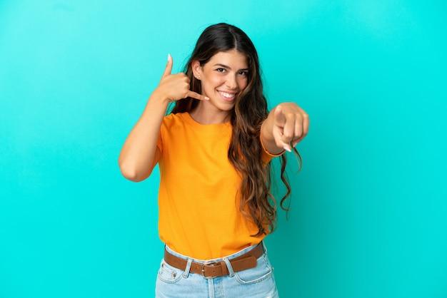 Молодая кавказская женщина изолирована на синем фоне, делая жест телефона и указывая вперед