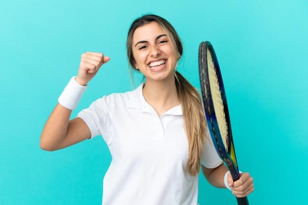 테니스를하고 승리를 축하 파란색 배경에 고립 된 젊은 백인 여자