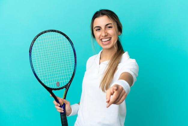 테니스를하고 앞을 가리키는 파란색 배경에 고립 된 젊은 백인 여자