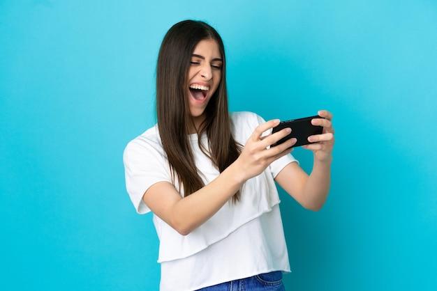 携帯電話で遊んで青い背景に分離された若い白人女性