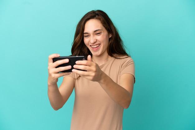 Молодая кавказская женщина изолирована на синем фоне, играя с мобильным телефоном