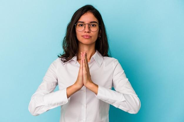 祈り、献身を示し、神のインスピレーションを探している宗教的な人を祈って青い背景に孤立した若い白人女性。