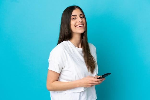 모바일로 메시지 또는 이메일을 보내는 파란색 배경에 고립 된 젊은 백인 여자