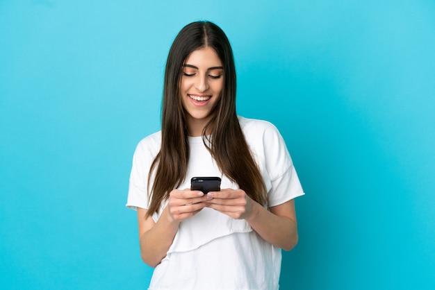 携帯電話でメッセージやメールを送信する青い背景で隔離の若い白人女性