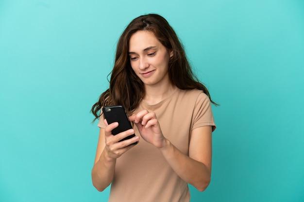 Молодая кавказская женщина изолирована на синем фоне, отправляя сообщение или электронное письмо с мобильного телефона