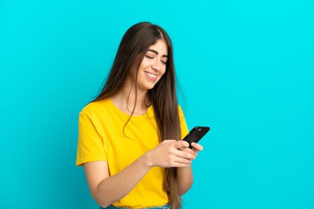 모바일 메시지를 보내는 파란색 배경에 고립 된 젊은 백인 여자