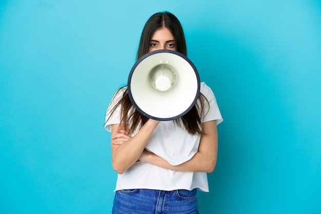 何かを発表するためにメガホンを介して叫んで青い背景で隔離の若い白人女性