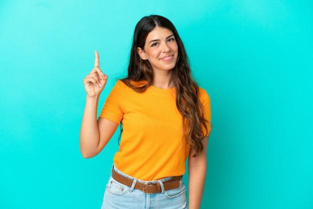 Молодая кавказская женщина изолирована на синем фоне, показывая и поднимая палец в знак лучших