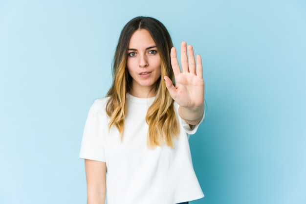 青の背景に孤立した若い白人女性は、一時停止の標識を示している手を伸ばして立って、あなたを妨げています。