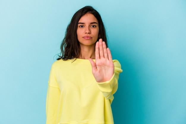 Молодая кавказская женщина, изолированные на синем фоне, стоя с протянутой рукой, показывая знак остановки, предотвращая вас.