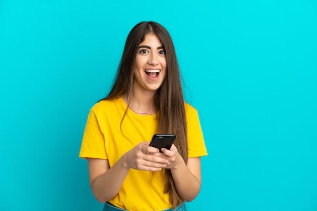Молодая кавказская женщина, изолированная на синем фоне, удивлена и отправляет сообщение