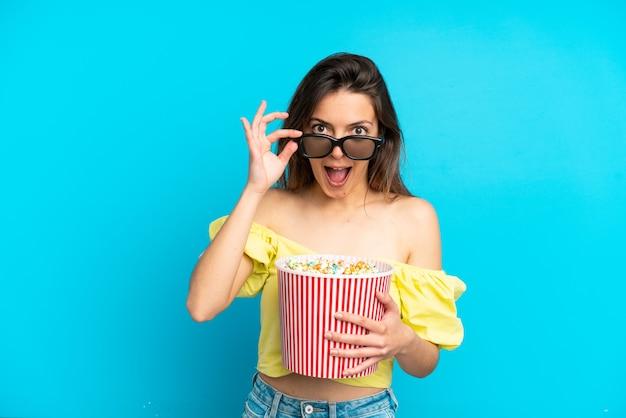 파란색 배경에 격리된 젊은 백인 여성은 3d 안경에 놀라고 큰 팝콘 양동이를 들고 있다