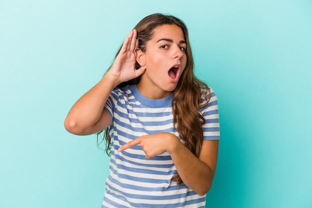 ゴシップを聴こうとしている青い背景で隔離の若い白人女性。