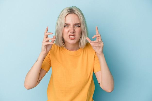 青い背景に孤立した若い白人女性は、緊張した手で叫んで動揺します。