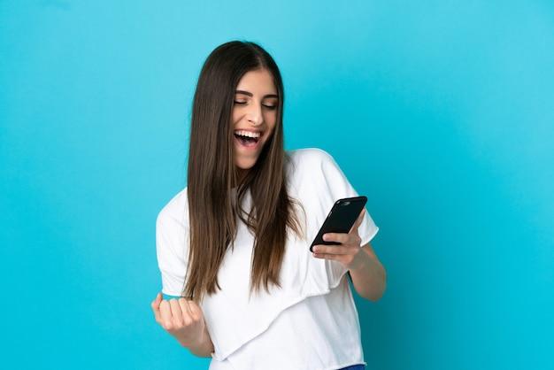 携帯電話を使用して勝利のジェスチャーをしている青い背景で隔離の若い白人女性