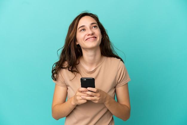 携帯電話を使用して見上げる青い背景で隔離の若い白人女性