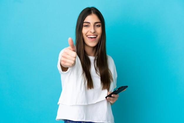 親指を立てながら携帯電話を使用して青い背景で隔離の若い白人女性