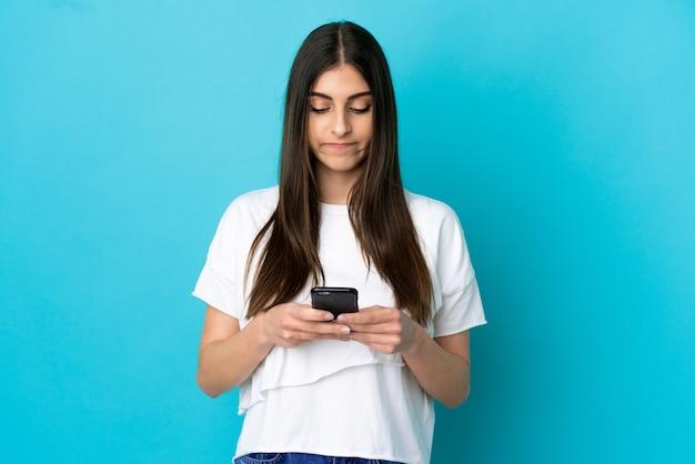 携帯電話を使用して青い背景で隔離の若い白人女性