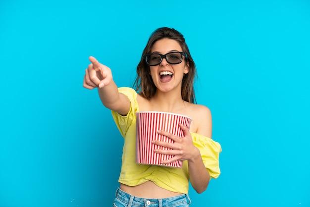 Молодая кавказская женщина изолирована на синем фоне в 3d-очках и держит большое ведро попкорна, указывая в сторону