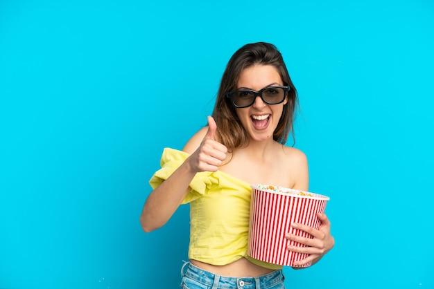 Молодая кавказская женщина изолирована на синем фоне в 3d-очках и держит большое ведро попкорна, указывая вперед