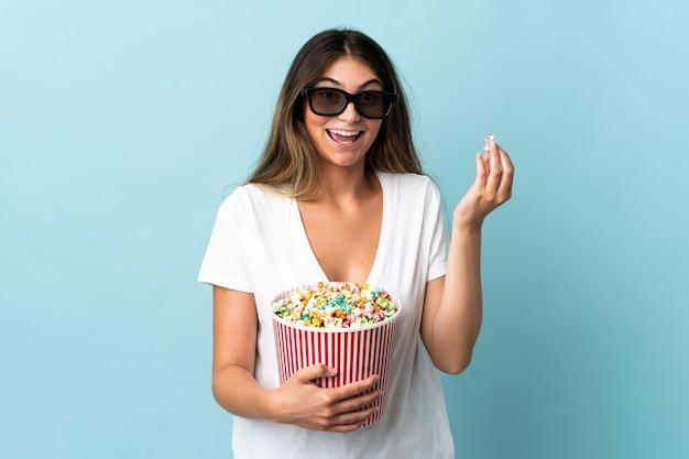 3dメガネとポップコーンの大きなバケツを保持している青い背景で隔離の若い白人女性