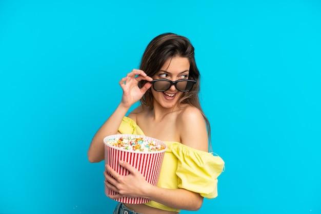 3d 안경을 쓰고 파란색 배경에 고립되어 큰 팝콘 양동이를 들고 있는 백인 젊은 여성