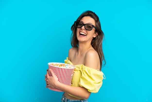 Молодая кавказская женщина изолирована на синем фоне в 3d-очках и держит большое ведро попкорна
