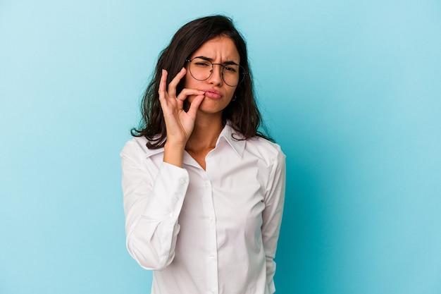 Молодая кавказская женщина изолирована на синем фоне с пальцами на губах, сохраняя в секрете.