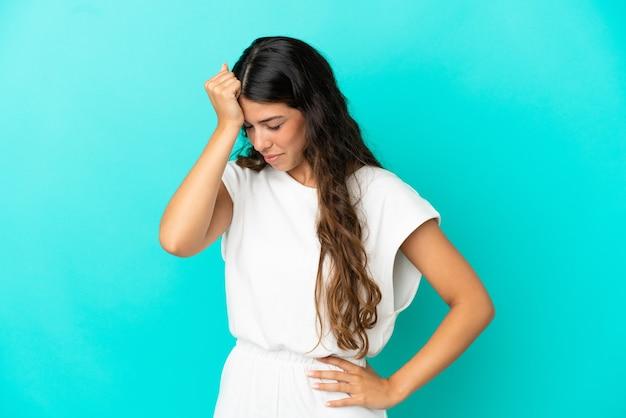 頭痛と青い背景で隔離の若い白人女性