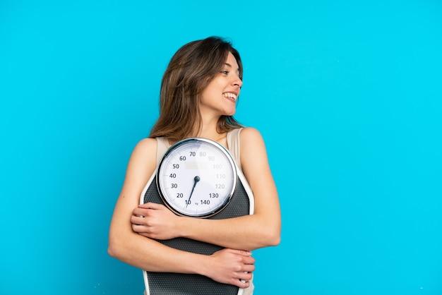 Молодая кавказская женщина изолирована на синем фоне с весами и смотрит в сторону