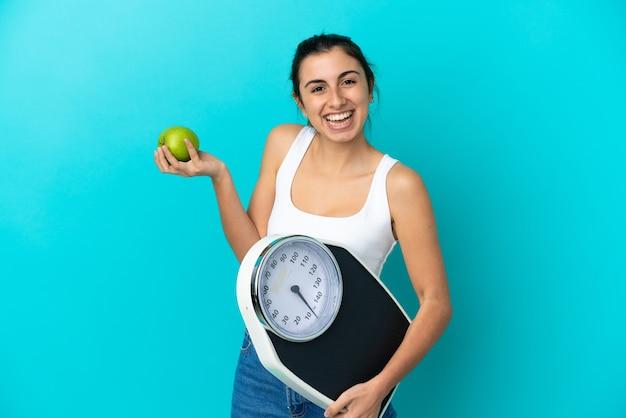무게 기계와 사과와 파란색 배경에 고립 된 젊은 백인 여자